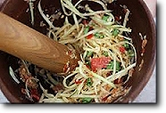 Green Papaya Salad traditionally prepared in a Thai mortar & pestle